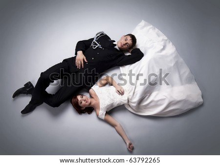 Romantic image of just married couple laying on the floor together and looking at each other - stock photo