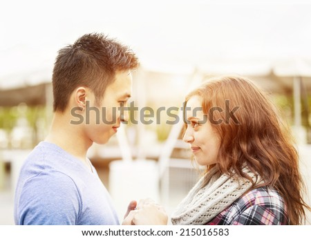 Romantic interracial young couple holding hands and looking at each other outside in sunset light - stock photo