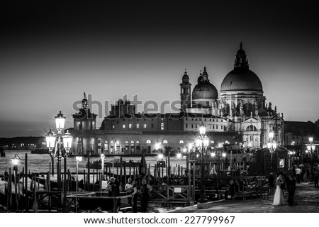 Romantic Italian city of Venice in black and white. World Heritage Site. Traditional Venetian wooden boats, gondolier and Roman Catholic church Basilica di Santa Maria della Salute. - stock photo