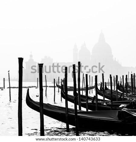 Romantic Italian city of Venice (Venezia), World Heritage Site: traditional Venetian wooden boats, gondolier and Roman Catholic church Basilica di Santa Maria della Salute in the misty background. B&W - stock photo