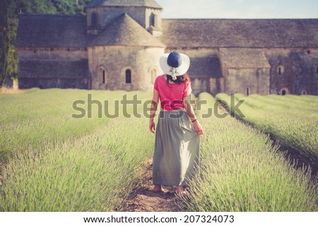 Romantic lady in lavender field. An ancient monastery in background, relaxing and enjoying. - stock photo