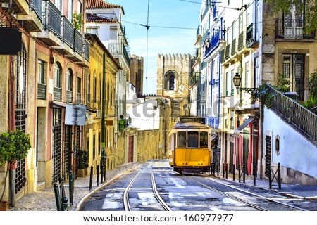 Romantic Lisbon street with the typical yellow tram and Lisbon Cathedral on the background  - stock photo