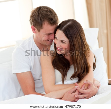 Romantic lovers embracing lying in bed at home - stock photo
