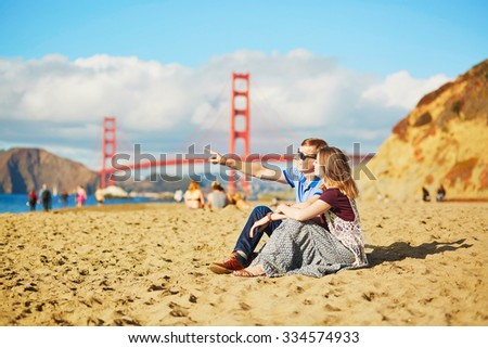 Romantic loving couple having a date on Baker beach in San Francisco, California, USA. Golden gate bridge in the background - stock photo