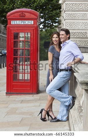 Romantic man and woman couple next to traditional red telephone box in Westminster, London, England, Great Britain - stock photo