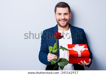 Romantic man. Handsome young man giving a gift and a flower to you while standing against grey background - stock photo
