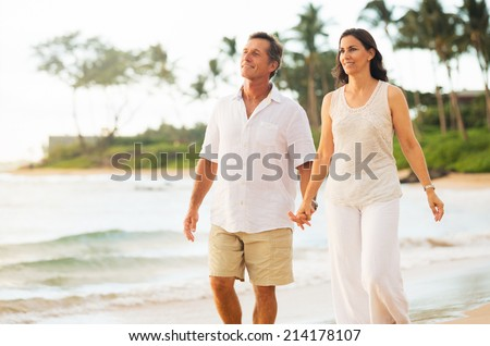 Romantic Mature Couple Enjoying Walk on the Beach - stock photo