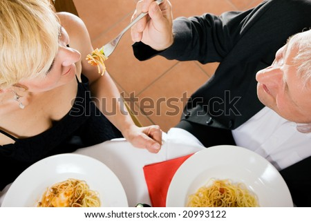 Romantic mature couple having dinner, he feeding her with delicious pasta - stock photo