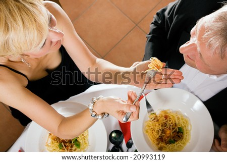 Romantic mature couple having dinner, she feeding him with delicious pasta - stock photo