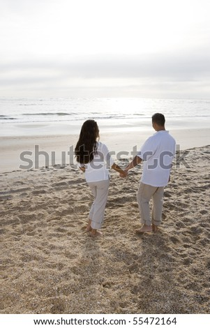 Romantic mid-adult Hispanic couple watching sunrise at beach - stock photo