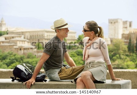 Romantic middle aged couple on wall looking at each other; Granada; Spain - stock photo