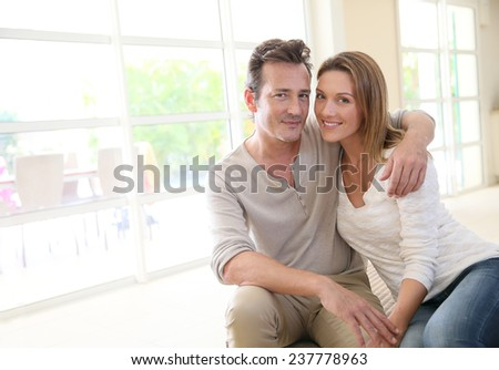 Romantic middle-aged couple sitting on couch - stock photo