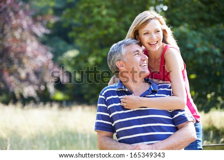 Romantic Middle Aged Couple Walking In Countryside - stock photo