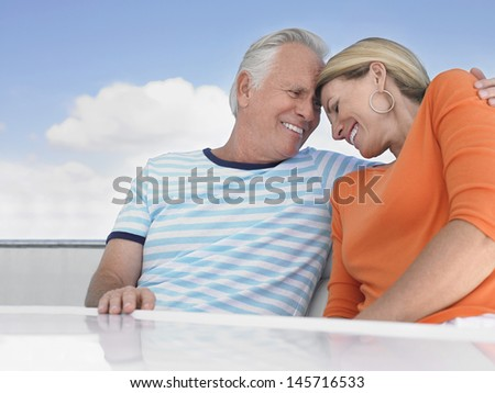 Romantic middle aged couple with arm around on yacht - stock photo