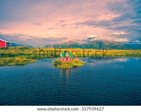 Romantic miniature scandinavian red house on tiny islet - stock photo