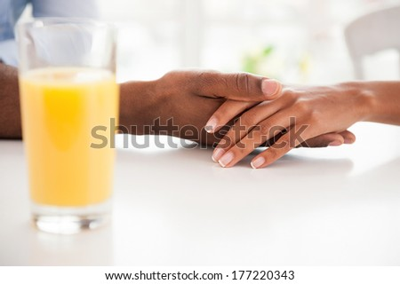 Romantic moment. Close-up of African couple holding hands while sitting at the table with orange juice on the foreground  - stock photo