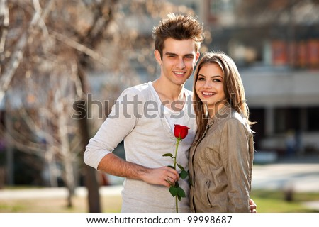 romantic moment: young man giving a rose to his girlfriend - stock photo