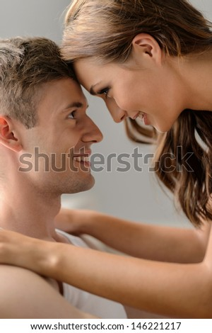 Romantic mood. Close up of beautiful young couple looking at each other and smiling - stock photo