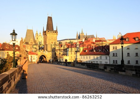 Romantic morning View on the Prague gothic Castle and St. Nicholas' Cathedral with the Charles Bridge baroque Statues, Czech Republic - stock photo