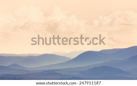 Romantic mountain landscape in pastel colors. Sunrise at the hills. Landscape with blue mountainous silhouette. Scenic view of ridge mountains in foggy weather. - stock photo