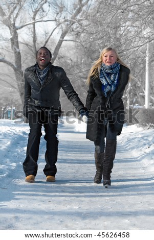 Romantic multi-etnic couple is running in the winter park - stock photo