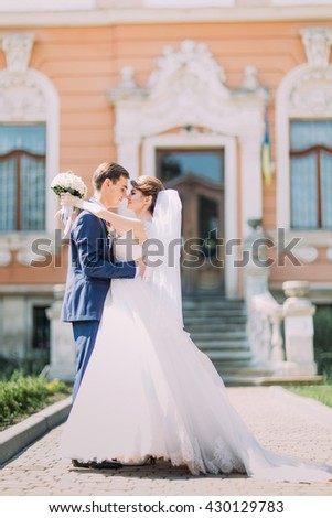 Romantic newly married couple charming bride and stylish groom holding each other in front of antique building entrance - stock photo