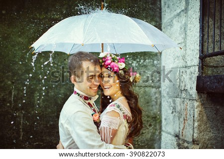 Romantic newlyweds in traditional ethnic dress under umbrella - stock photo