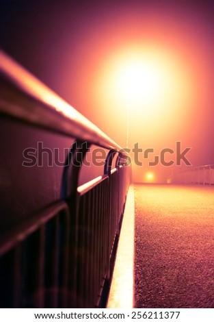 Romantic night city walk on a bridge with street lights (toned, diffused).  - stock photo