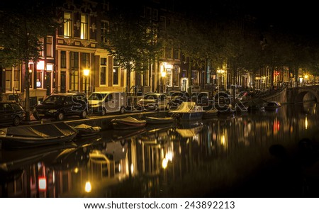 Romantic nocturnal view of Amsterdam: canal in the Red District. Buildings, cars and boats are reflected in the water  - stock photo