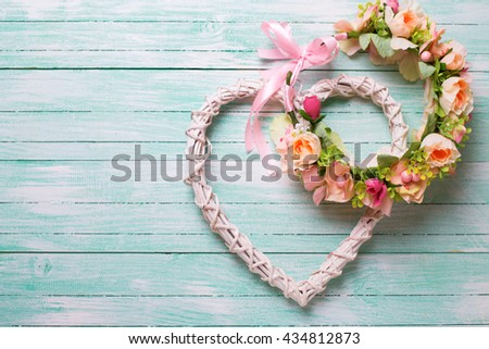 Romantic or wedding background. Flower wreath and decorative heart  on turquoise  wooden background. Selective focus. Place for text. - stock photo