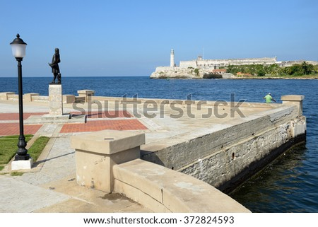 Romantic park in Havana with a view of the castle and lighthouse of El Morro at the bay entrance - stock photo