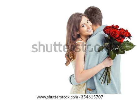Romantic photo of beautiful couple on white background. Beautiful young woman hugging her boyfriend and holding nice bouquet of red roses - stock photo
