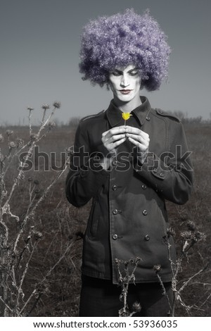 Romantic photo of the clown outdoors holding yellow flower - stock photo