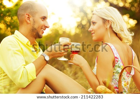 Romantic picnic concept. Portrait of a young loving couple in trendy casual clothes drinking red wine and enjoying each other. Sunny summer (autumn) day. Outdoor shot - stock photo