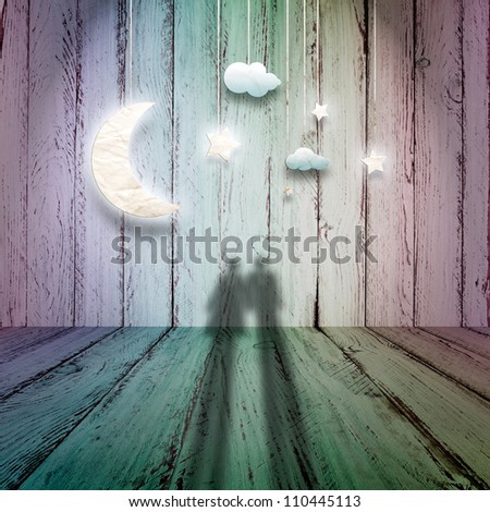 Romantic picture with loving couple looking at the paper stars, the clouds and the moon on a vintage wooden background - stock photo