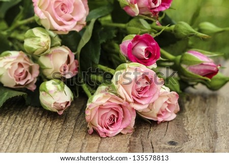 Romantic pink roses on wooden table - stock photo