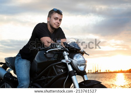 Romantic portrait handsome biker man in sunglasses sits on a bike on a sunset near lake and city - stock photo