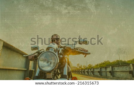 Romantic portrait handsome biker man in sunglasses sits on a bike on a sunset on old rusty metal bridge in city against house and sunny sky background Empty copy space for inscription - stock photo