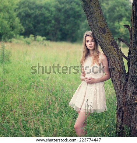 Romantic portrait of a beautiful blonde in a summer field - stock photo