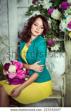 Romantic portrait of pretty young woman with flowers. Yellow dress and pink flowers.  - stock photo