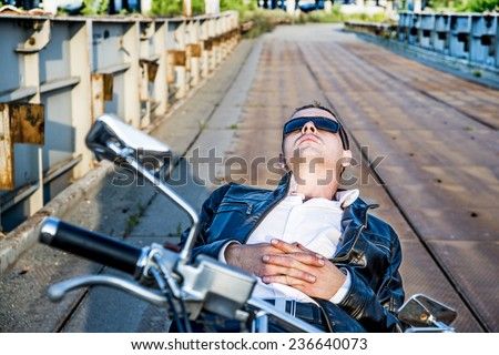 Romantic portrait resting relax handsome biker man in sunglasses sits on a bike on a sunset on old rusty metal bridge in city against house and sunny sky background Empty copy space for inscription - stock photo