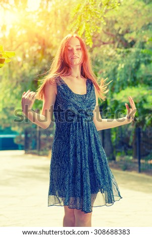 Romantic redhead women in blue dress posing outdoors. Toned in instagram style. Backlit by sun. - stock photo