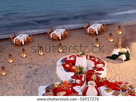 Romantic restaurant setting on a beach - stock photo