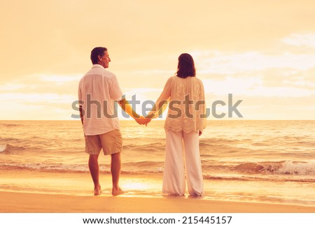 Romantic Retired Couple Relaxing on Beach Vacation at Sunset - stock photo