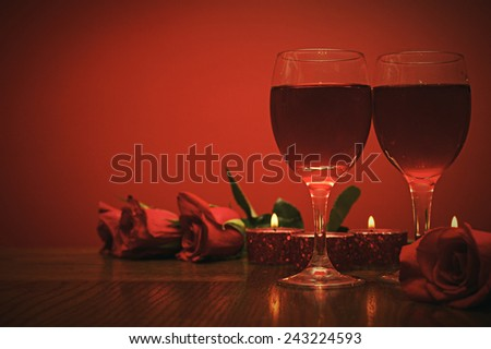 Romantic retro card a glasses of vine with red roses and candles  - stock photo