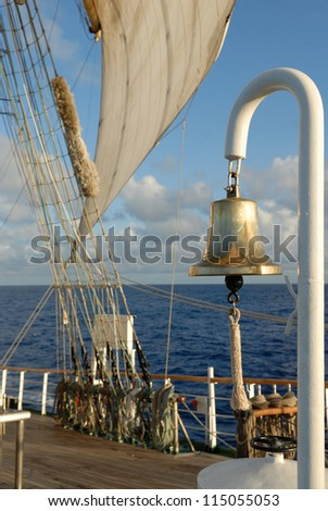 Romantic Sailing. Bell and sea sail on the ocean background - stock photo