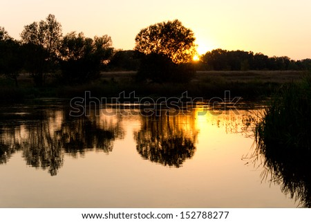 Romantic scenic nature image with sunlight reflected in the surface of a lake at sunset - stock photo