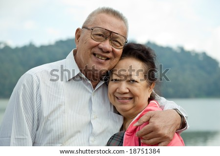 romantic senior couple on lake - stock photo