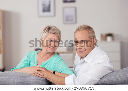 Romantic Senior Couple Sitting at the Living Room with Holding Hands And Arms Leaning on the Edge of the Couch. - stock photo