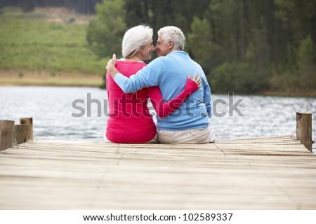 Romantic senior couple sitting on a jetty - stock photo